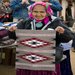 May Shay, one of our Big Mountain Elders who attends the rug show, holds one of her weavings at a recent food run.