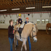 A physical therapist utilizing the horse's movement duirng a therapy session.