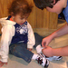 Nichols Lowinger, helping a child with her new sneakers