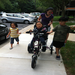 Alice riding a bike accompanied by her siblings Benjamin and Bailey