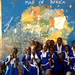 A group of female students pose in front of their school map in The Gambia.