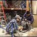 Bikery co-op member teaches youth how to repair a flat