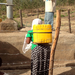 A woman carrying a jug of water from a clean well. She only has to travel a few yards thanks to this local well!