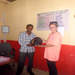 Jaime giving the principal a bag of school supplies. All supplies were given to students who are orphans.