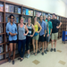 A group of volunteers pose next to the first shelves of organized books.