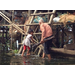 Granmother and grandchild wade through water to get home (Kampong Phluk, Cambodia)