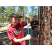 This camper is demonstrating how to use an increment borer, a tool used to determine tree age.